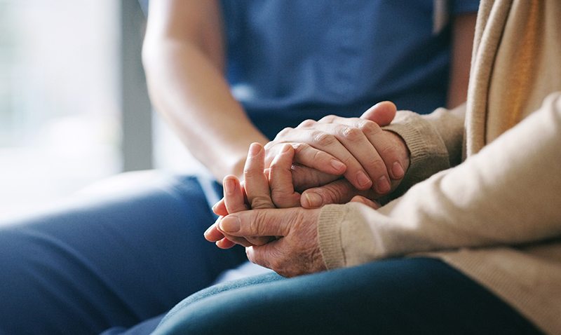 Closeup of senior and adult holding hands.